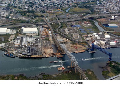 Aerial highway interstate truss river rail bridge, tug boat barge, industrial manufacturing production plant, sewage treatment plant, green grass river front, construction site, shipping port