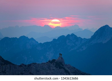 AERIAL: Hiker couple stands on a rocky mountain peak and watch the sunrise. Breathtaking shot of golden morning sun rising from behind the mountains and illuminating the tourists standing on a cliff.