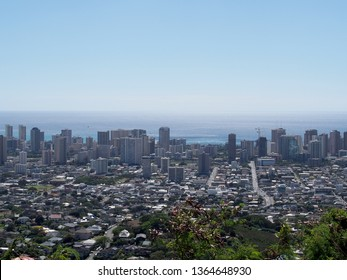 Aerial of Honolulu, Waikiki, Buildings, parks, streets, hotels and Condos with Pacific Ocean stretching into the ocean on nice day on Oahu.