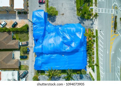 Aerial image of a building with blue fumigation tent