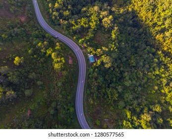 Aerial image car driving along the winding mountain pass road through the forest - Travel Concept