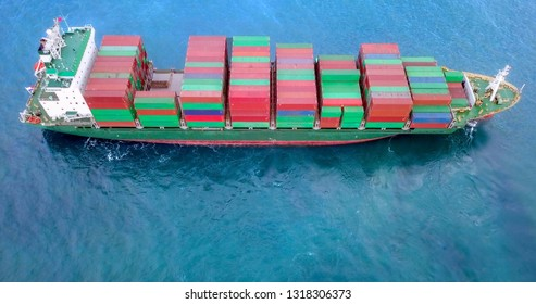 Aerial image of a container ship at sea, loaded with various container brands.