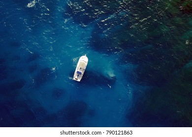 Aerial image of a diving boat above blue clear waters. Location: Ochos Rios, Jamaica, Caribbean Sea.