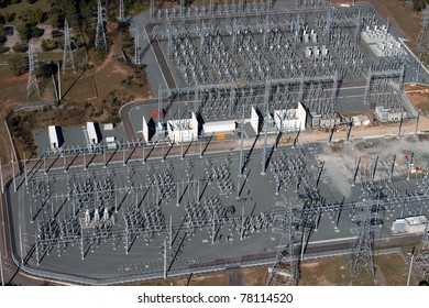 Aerial image of electrical substation featuring wires, transformers and large scale power energy towers.