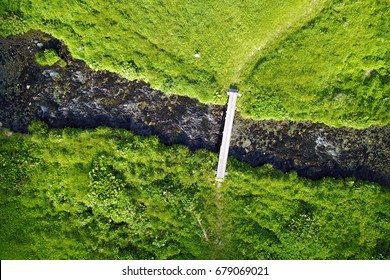 Aerial image of a foot crossing over a mountain stream surrounded by beautiful green pastures. Location Lake Louvie, Swiss Alps.