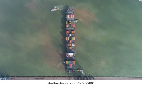 Aerial image of a large container ship swinging in a turning basin assisted by four tugs in a shallow-water harbour (Itajai-Navegantes, Brazil)