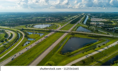 Aerial image of a modern highway interchange with green grass landscape and lakes