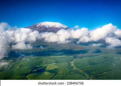 Aerial image of Mount Kilimanjaro, Africa's highest mountain, with snow and white puffy clouds from Kenya