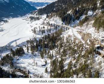 Aerial image of a mountain valley in Alps in snowy winter season with railway viaduct at the background