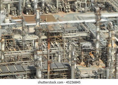 Aerial image of oil refinery featuring blurred fumes from stack.