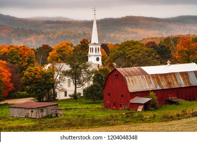 Aerial image of Peachem vermont near New Hampshire with town below and white church with a red barn during Autumn with Fall Colors in the Foliage vibrant yellow orange and red leaves drop misty