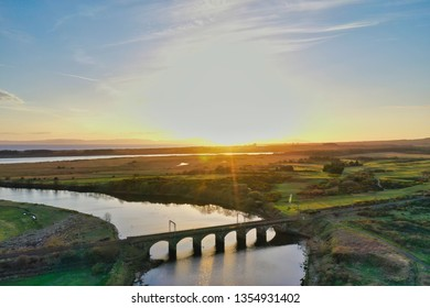 Aerial image of a Scottish coastal sunset over an arched railway bridge