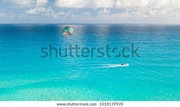 Aerial image showing a boat and para sailing in the middle of a very beautiful crystal clear blue water ocean of the Caribbean in Cancun, Mexico.