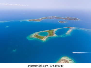 An aerial image of a speedboat moving through various cayes and coral reefs off the coast of Belize.