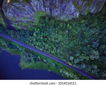 Aerial image of tree tops below Vista House in the shadow of the rock cliffs in the Columbia Gorge
