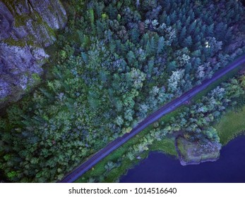 Aerial image of tree tops and railroad tracks below Vista House in the shadow of the rock cliffs in the Columbia Gorge