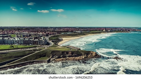 Aerial Image of Tynemouth. Longsands Beach with waves crashing into the shoreline. Great view up the North East Coast of North Tyneside.