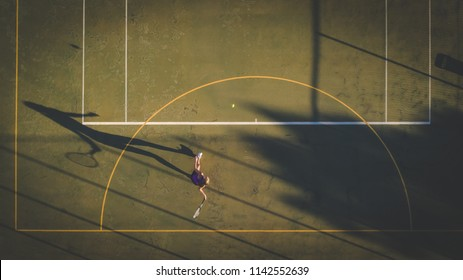 Aerial image of a young woman playing tennis on a tennis court shot from overhead with a drone