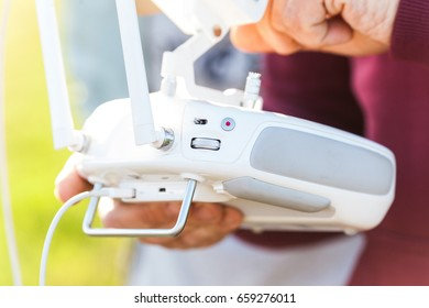 aerial imagery and tech hobby, recreation concept - closeup on white remote radio control in pilot hands, modern high-tech solution for video filming and joy flying
