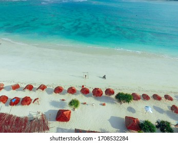 Aerial Kuta Beach Lombok. View of nice empty sandy beach with umbrella and beach chair, turquoise water. Luxury Beach