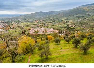 Aerial landscape with a cemetery among olive trees in the valley at the feet of the hills. View from Cortona in Tuscany, Italy.