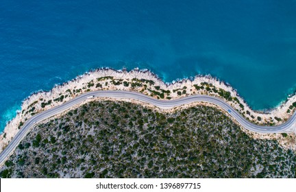 Aerial landscape of coastline and a road seascape. Car drives down the empty asphalt road running along the sunny Mediterranean shoreline of Turkey. Tourist car cruises down the scenic coastal road .