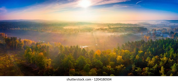 Aerial landscape with foggy sunrise over meadows and forest. Polish landscape.