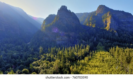 Aerial landscape shot from 400 feet of hazy smoke from close by forest fires covers the craggy spires and hills in the Columbia River Gorge near Portland Oregon