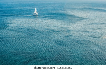 aerial landscape of south sea vivid blue water surface and small white single yacht far from shot point, tourism and summer vacation holidays concept, copy space