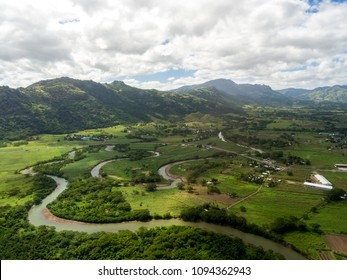 Aerial Landscape View of Lush Green Sugar Cane Farm Land with Winding River Beneath the Mountains, Pacific Island, Nadi, Fiji