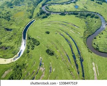 Aerial landscape of winding river in green fields
