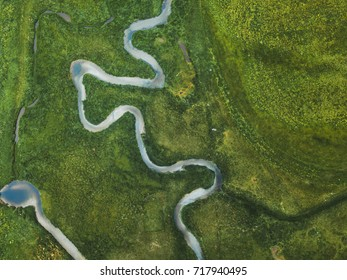 aerial landscape of winding river in green field, top view of beautiful nature texture from drone