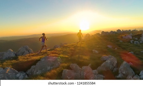 AERIAL, LENS FLARE: Athletic young couple jogging along a scenic grassy trail in the beautiful mountains in Slovenia. Flying along sporty woman and her boyfriend trail running along a grassy hill.