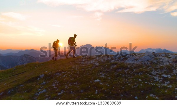 AERIAL, LENS FLARE: Carefree young trekkers on an active summer vacation hiking uphill on a picturesque summer morning. Tourist couple exploring the stunning Julian Alps at sunrise. Fun recreation.