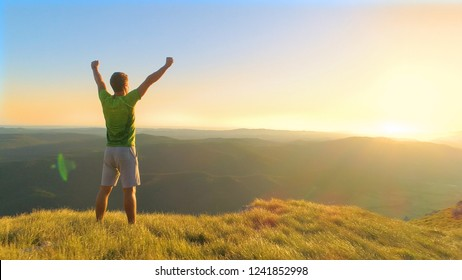 AERIAL, LENS FLARE, COPY SPACE: Unrecognizable athletic male outstretches arms while watching the picturesque sunset from a grassy mountain. Bright golden morning sunbeams shine on victorious hiker.