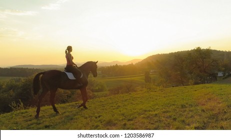 AERIAL, LENS FLARE: Flying along young woman riding her beautiful brown horse at sunrise. Happy Caucasian girl trotting on her horse through the idyllic countryside. Picturesque sunset in Slovenia.