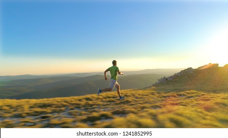 AERIAL, LENS FLARE: Flying behind athletic young man sprinting down a grassy hill at sunset. Cinematic shot of fit male fell running in the scenic mountains in Slovenia on a sunny summer evening.