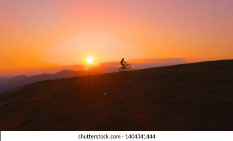 AERIAL, LENS FLARE, SILHOUETTE: Unrecognizable man riding a mountain bike does a wheelie while riding uphill to meet his friends at the mountaintop. Mountain bikers meet up at dawn to ride downhill.