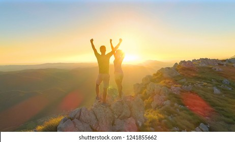 AERIAL, LENS FLARE: Unrecognizable hiker couple outstretches arms after reaching the grassy mountain summit at sunset. Man and woman celebrate reaching the top of the hill on a sunny summer evening.
