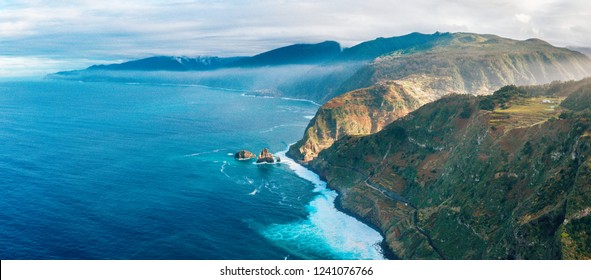 Aerial Madeira island view with Atlantic ocean, white waves, cliffs and green nature