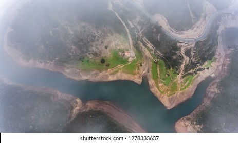 Aerial. Magical view from the sky through the clouds and fog, the reservoir Odelouca.