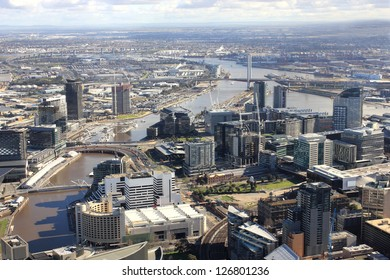 Aerial melbourne city view with tall buildings and river running through middle