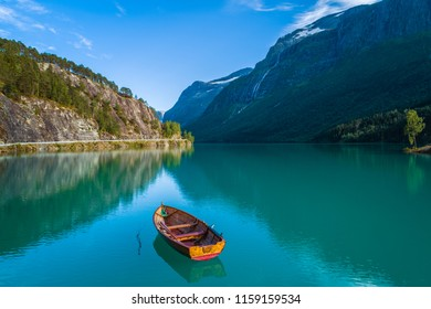 Aerial midday view of Lovatn lake - the greenest lake in Norway - with surrounding mountains and lonely colorful rowing boat in the middle at summer in Norway