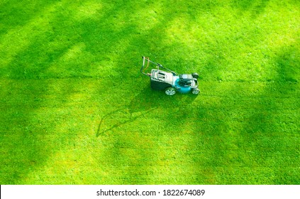Aerial mowing lawns. Top aerial view lawn mower on green grass. Mower grass equipment. Mowing gardener care work tool close up view. Sunny day.