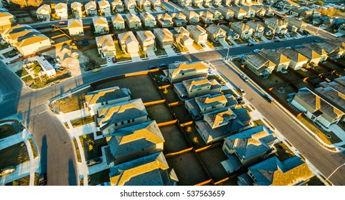Aerial new housing community suburb neighborhood outside of Austin texas USA near round rock. Morning sunshine with frozen rooftops golden hour
