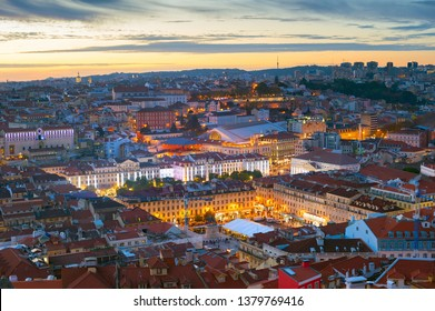 Aerial night cityscape of Lisbon downtown, red rooftops, illuminated Praca do Pedro IV square, afterglow skyline, Portugal