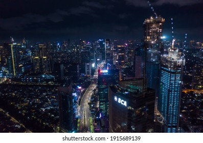 Aerial night view of high rise skyscrapers under construction and modern city center with multi lane highway in Jakarta, Indonesia in 2021