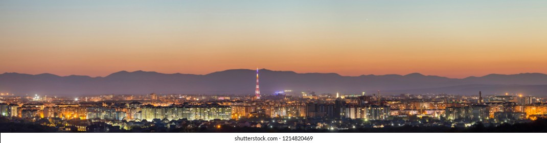Aerial night view of Ivano-Frankivsk city, Ukraine. Bright lights of tall buildings, high television tower and suburbs cottages roofs on distant mountains and clear sky with first star background.