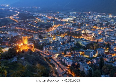 Aerial night view of the town of Martigny in Valais, Switzerland. Chateau de la Batiaz is overlooking the scene.