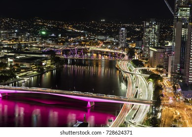 Aerial nightscape over Brisbane CBD, with a view of city traffic over Victoria Bridge and Pacific highway entrances into the city including North Quay.